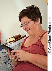 Frau schmunzelt mit eBook - Frau mit einem eBooks