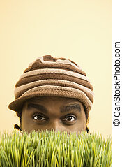 Man hiding in grass. - African-American mid-adult man...