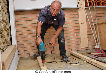 Facharbeiter bei Renovierungsarbeiten - Bodenleger befestigt...
