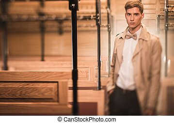 Handsome young man in coat inside vintage train coach
