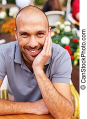 Positive middle-aged man alone behind table in summer cafe