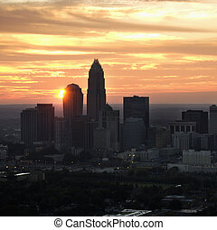 Charlotte, NC skyline - Aerial view of sunset behind city...