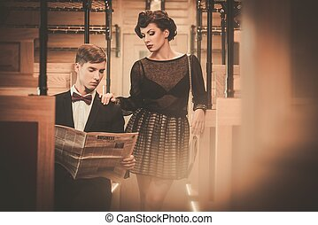 Beautiful vintage style couple reading newspaper inside...
