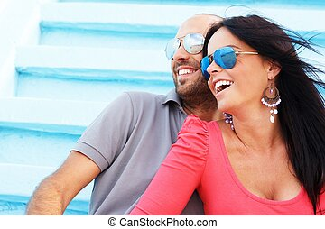 Happy smiling middle-aged couple with beach reflected in...