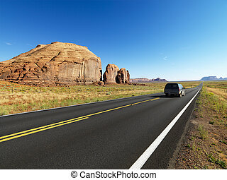 Desert road - Sport utility vehicle on open highway in...