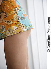 Female legs in short dress. - Side view of buttocks and legs...