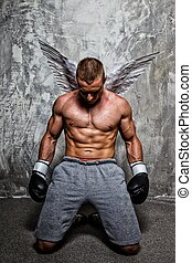 Young boxer with angel wings behind his back standing on his...