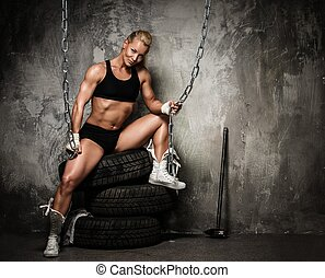 Beautiful muscular bodybuilder woman sitting on tyres and...