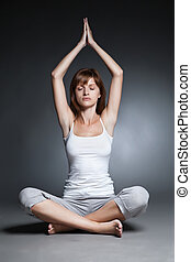 Young woman doing yoga against dark background