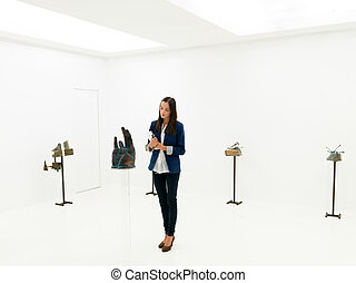 art critic studying contemporary artworks - young caucasian...