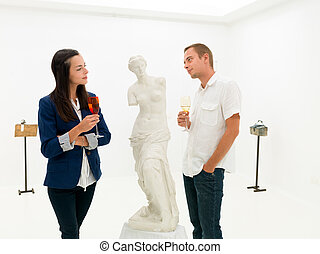 people studying fine art statue in museum