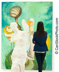 female art coollector at art gallery - woman looking at...