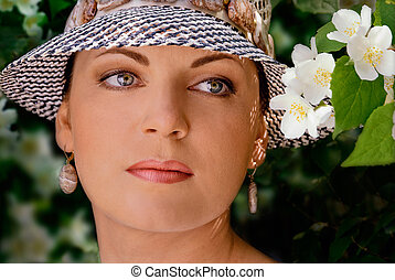 Portrait of a mature woman in a hat with jasmine flowers