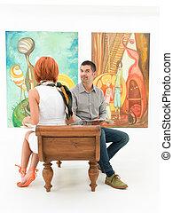 people looking at colorful paintings in art gallery