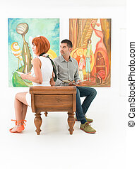 couple admiring artworks - two caucasian people sitting on a...