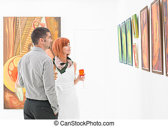 people looking at art gallery paintings - young caucasian...