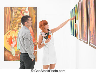 artist showing work in art gallery - young attractive woman...