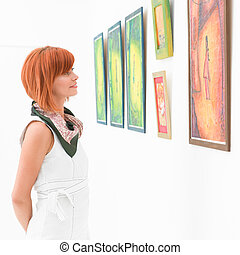 woman admiring a painting in a museum