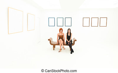 happy women in art gallery - front view of two happy women...