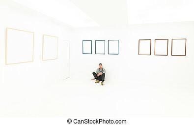 relaxed man sitting on a floor in art gallery