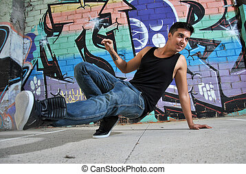 breakdance dancer on a city street posing with a dance move
