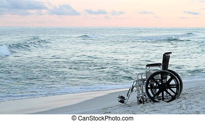 Wheelchair Beach - Empty vacant wheelchair sits on the sand...
