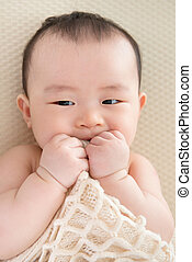 Teething Asian baby girl - Adorable six months old teething...