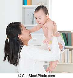 Asian mother and baby at home. - Asian mother and six months...