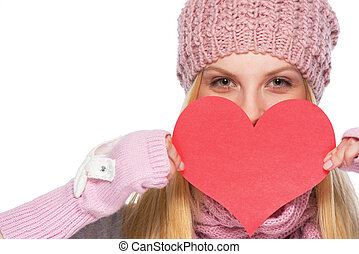 Happy girl in winter clothes hiding behind heart shaped...
