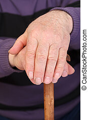 Old man's worker hand resting on the walking stick