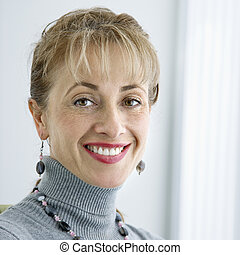 Woman smiling. - Pretty Caucasian woman smiling at viewer.