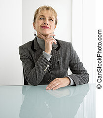 Woman thinking. - Caucasian woman sitting at desk with hand...