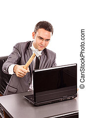 Young businessman with a hammer ready to smash his laptop...