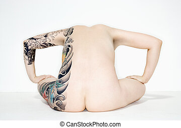 Nude Woman sitting - Nude caucasian woman with tattoos on...