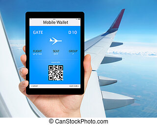 man hand holding the tablet with mobile wallet and plane ticket against the background of the window with blue sky and airplane wing