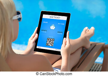 beautiful girl in a bathing suit lying on a deck chair by the pool and holding a tablet computer with mobile wallet and liner ticket on a screen