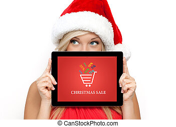 blonde girl in a red Christmas hat on New Year, holding tablet computer with christmas sale on a screen