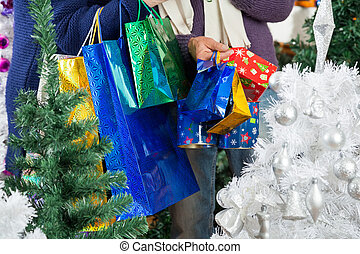 Shopaholic Couple Carrying Shopping Bags At Christmas Store...