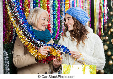 Mother And Daughter Shopping For Tinsels - Happy mother and...