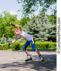 Teenage girl roller blading in a skate park passing the...