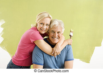 Couple with paintbrushes. - Portrait of smiling adult couple...