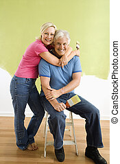 Couple with paintbrushes - Portrait of smiling adult couple...