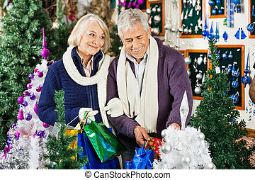 Couple Shopping In Christmas Store - Senior couple shopping...