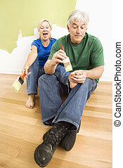 Man pretending to paint woman\'s toenails. - Middle-aged...