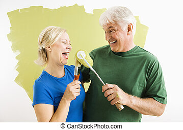 Man and woman relaxing while painting. - Middle-aged couple...