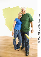 Man and woman with half-painted wall. - Middle-aged couple...
