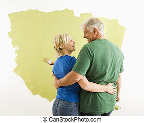Man and woman discussing paint job. - Middle-aged couple...