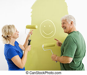 Couple laughing at smiley face painting. - Middle-aged...