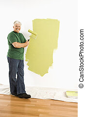 Man painting wall - Middle-aged man painting wall green with...