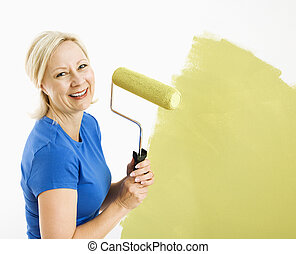 Woman painting wall. - Middle-aged woman painting wall green...